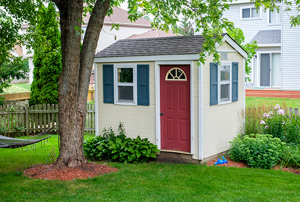 A cream shed with a red door in backyard